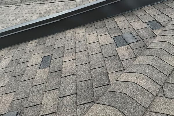 Roof damage caused by shingles blowing off